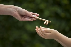 adult handing a key to a child