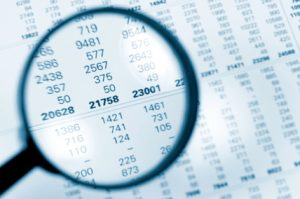 magnifying glass over financial records